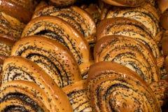 Molti panini, popovers con la bugia una dei semi di papavero su un altro, pasticcerie fresche del rotolo di cannella immagine stock
