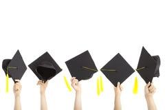 Molti passano i cappelli di graduazione della holding Immagini Stock