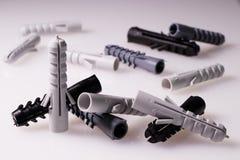 Molti perni della plastica su fondo bianco Fotografie Stock
