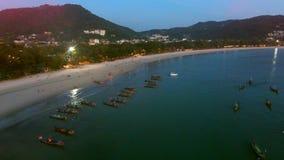 Molti pescherecci sono sull'ormeggio vicino alla spiaggia alla sera Immagine Stock