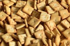 Molti piccoli biscotti sono a forma di quadrato Un modello di un salatino giallo Immagine di sfondo con pastr salato fotografia stock libera da diritti
