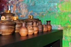 molti piccoli brocche e vasi dell'argilla che stanno su una tavola verde Fotografia Stock Libera da Diritti