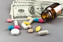 Molti pillole e soldi sui precedenti grigi Fotografia Stock Libera da Diritti