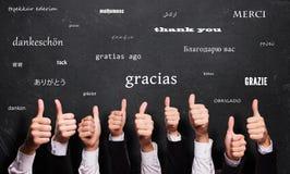 Molti pollici su con il ` di parola vi ringraziano ` in molte lingue davanti ad una lavagna fotografia stock libera da diritti