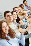 Riusciti studenti che tengono i pollici Immagini Stock