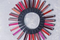 Molti rossetti colorati, diffusione fuori in un cerchio su un fondo bianco grigio chiaro fotografia stock