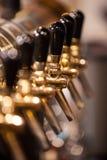 Molti rubinetti dorati della birra alla barra Immagine Stock