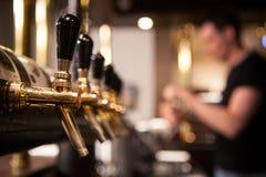 Molti rubinetti dorati della birra alla barra Fotografie Stock