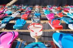 molti sandali di Flip-flop stati allineati su una corda Fotografie Stock