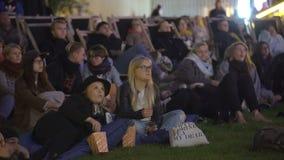 Molti spettatori nel cinema all'aperto nella sera stock footage