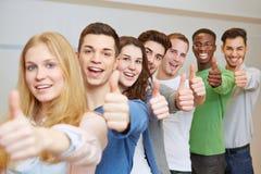 Studenti incoraggianti che tengono i pollici su Fotografia Stock Libera da Diritti