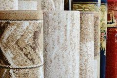 Molti tappeti variopinti nel deposito Decorazione Colourful del tessuto del negozio di Rolls del tappeto fotografia stock