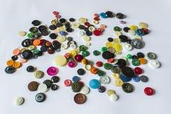 Molti tasti differenti Bottoni per i vestiti fatti di plastica I bottoni sono sparsi su un fondo leggero Molti tasti Fotografie Stock