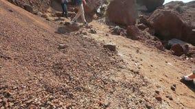 Molti turisti che camminano lungo il pendio pericoloso delle montagne vulcaniche di origine archivi video