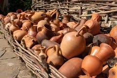 Molti utensili fatti a mano ceramici, fatti di argilla, appendenti sul recinto dell'acacia fotografie stock