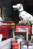 Molti vecchi veicoli raccoglibili del giocattolo nei colori luminosi su esposizione in un negozio di finestra Servizio della stra Immagini Stock
