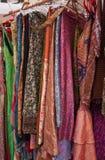 Molti vestiti variopinti che appendono per la vendita immagine stock libera da diritti