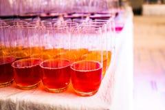 Molti vetri con la bevanda su una cena del buffet Immagine Stock
