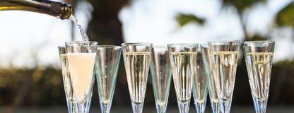 Molti vetri di champagne o del prosecco vicino allo stagno della località di soggiorno in un luxu Fotografia Stock
