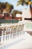 Molti vetri di champagne o del prosecco vicino allo stagno della località di soggiorno in un luxu Immagini Stock