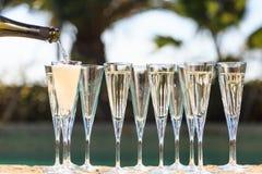 Molti vetri di champagne o del prosecco vicino allo stagno della località di soggiorno in un luxu Fotografia Stock Libera da Diritti