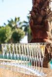 Molti vetri di champagne o del prosecco vicino allo stagno della località di soggiorno in un luxu Immagine Stock