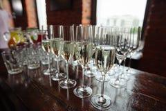 Molti vetri di champagne sopra il fondo di vetro della sfuocatura Fotografie Stock Libere da Diritti