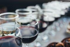 Molti vetri di vino differente in una fila sul contatore della barra Immagine Stock