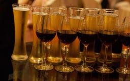 Molti vetri di vino differente in una fila sul contatore della barra immagini stock libere da diritti