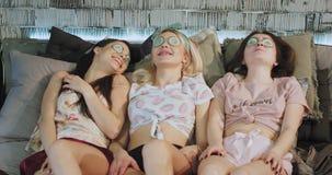 Molto abbastanza le signore si divertono a casa che sdraiano insieme sul letto e fanno una maschera di protezioni con le toppe, f stock footage