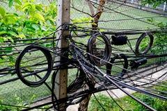 Molto confonda e scompigli i cavi elettrici sul palo elettrico fotografia stock