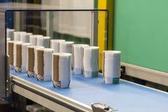 Molto fila della tazza di carta sul nastro trasportatore automatico durante il processo di fabbricazione in fabbrica immagine stock libera da diritti