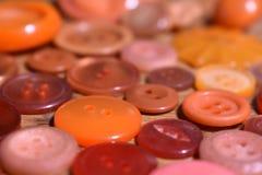 Molto il cucito arancio si abbottona su una tavola di legno Fotografia Stock