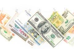 Molto le banconote in dollari sta appendendo su una corda con la molletta da bucato di legno isolata su fondo bianco fotografia stock libera da diritti