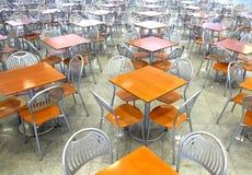 Molto quadrato marrone che mangia le tavole e le sedie del metallo che restano nel corridoio vuoto del caffè Fotografia Stock