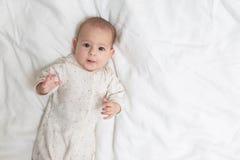 Molto sorpreso ed impressionato poca neonata che si trova su un letto bianco Copi lo spazio alla destra immagine stock libera da diritti