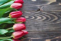 Molto tulipano rosso fiorisce sul backround di legno rustico da sopra fotografia stock
