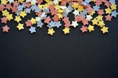 Molto zucchero ha colorato le stelle sopra la macro nera del fondo, fondo per i confettieri con copyspace fotografia stock libera da diritti