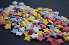 Molto zucchero ha colorato le stelle sulla macro nera del fondo, fondo per i confettieri fotografia stock libera da diritti