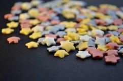 Molto zucchero ha colorato le stelle sulla macro nera del fondo, fondo per i confettieri con copyspace fotografia stock