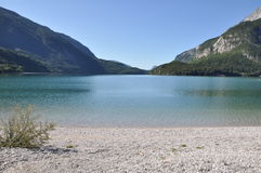 Molveno Lake, Italy. The Molveno Lake is located in Italy, Europe.  Images shows sandy beach in the front, silent water with small waves in the middle and Royalty Free Stock Photography