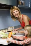 Mom's helper. Mother and daughter are cutting vegetables Royalty Free Stock Photography
