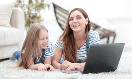 Mom και αυτή λίγη κόρη που χρησιμοποιεί ένα lap-top στο ελεύθερο χρόνο τους στοκ εικόνες