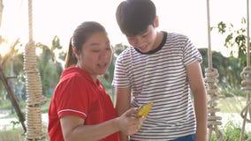 Mom και γιος που ταλαντεύονται στην ταλάντευση και που προσέχουν στο κινητό τηλέφωνο μαζί με το πρόσωπο χαμόγελου απόθεμα βίντεο