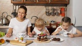 Mom και δύο κόρες έχουν ένα τσάι με το σπιτικό κέικ σοκολάτας στην κουζίνα, οικογενειακά γενέθλια στο σπίτι απόθεμα βίντεο