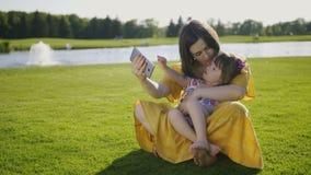 Mom και κάτω κορίτσι συνδρόμου που κάνουν selfies στο πάρκο απόθεμα βίντεο
