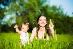 Mom και κοριτσάκι που βάζουν στη χλόη και χαρωπά που πιάνουν το σαπούνι β Στοκ Φωτογραφίες