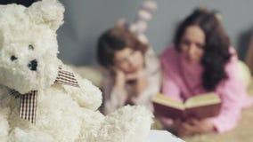 Mom και κόρη που βρίσκονται άνετα στο κρεβάτι, την ανάγνωση των παραμυθιών και να ονειρευτεί απόθεμα βίντεο