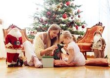 Mom και κόρη που εγκαθιστούν μπροστά από ένα χριστουγεννιάτικο δέντρο Στοκ εικόνες με δικαίωμα ελεύθερης χρήσης