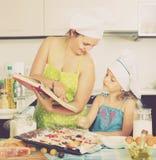 Mom και κόρη που διακοσμούν την πίτσα Στοκ Εικόνες